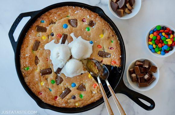 Spoons digging in to Halloween Candy Skillet Cookie topped with vanilla ice cream