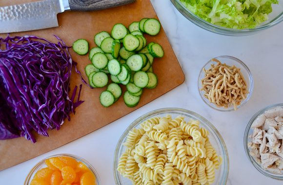 Cutting board with shredded red cabbage, diced cucumbers and knife next to small bowls containing lettuce, chow mein noodles, shredded chicken, pasta and mandarin oranges