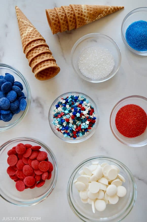 Various sized bowls with red, white, and blue sprinkles and candy melts next to waffle cones