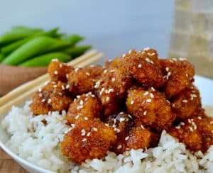 A white bowl containing white rice topped with sesame chicken and chopsticks on the side