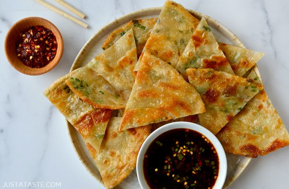 A plate with scallion pancakes cut into wedges and soy dipping sauce