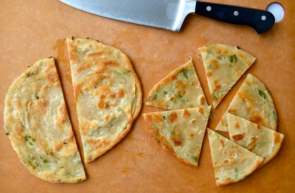 A cutting board with a knife and scallion pancakes cut into wedges