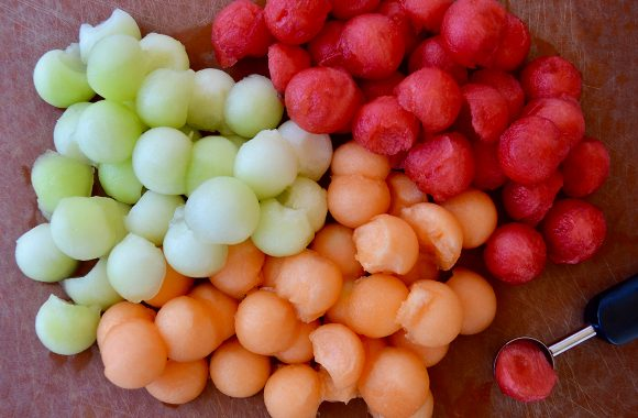 Melon baller next to cantaloupe balls, honeydew melon balls and watermelon balls