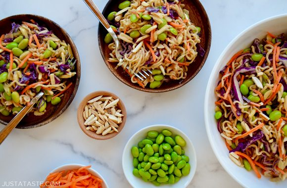 Easy ramen noodle salad in various sized bowls next to smaller bowls with edamame, slivered almonds and shredded carrots