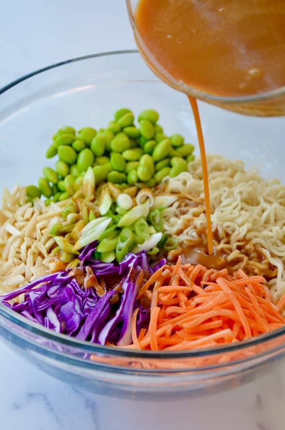 Peanut dressing being poured over carrots, cabbage, scallions, edamame and noodles in a bowl