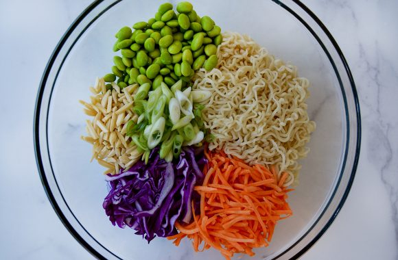 Clear bowl containing ramen noodles, shredded carrots and purple cabbage, sliced scallions, slivered almonds and shelled edamame