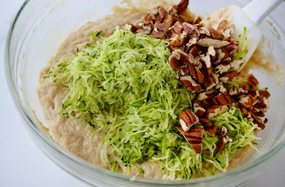 Glass bowl containing shredded zucchini, chopped pecans and muffin batter