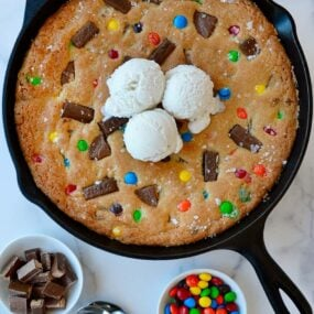 Leftover Halloween Candy Skillet Cookie topped with vanilla ice cream next to small bowls containing chocolate candy