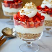 Small glass dessert cup containing crushed pretzels, no-bake cheesecake and sliced strawberries topped with homemade whipped cream.