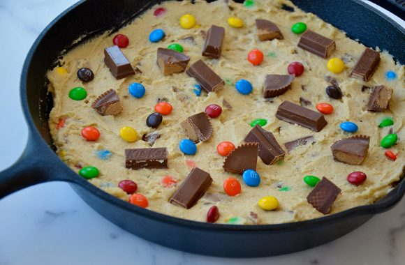 Cast iron skillet containing unbaked cookie dough topped with chopped candy