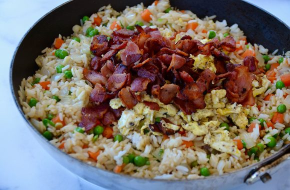 Large skillet with peas, carrots, onions, rice, eggs and bacon