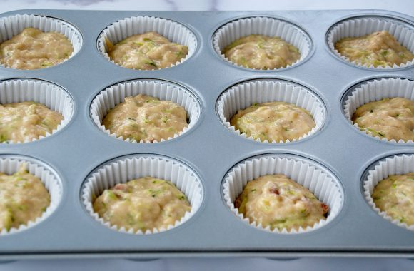 Muffin tin lined with paper filled with batter