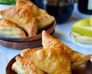 Mini Fruit and Cheese Turnovers on brown plate with glasses of red wine in background