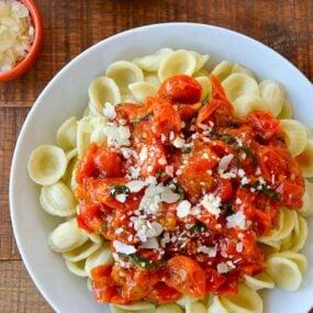 Top down view of quick cherry tomato pasta sauce over orecchiette