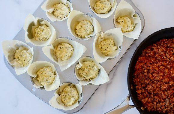 Muffin pan with wonton wrappers filled with ricotta cheese mixture next to skillet with Italian sausage