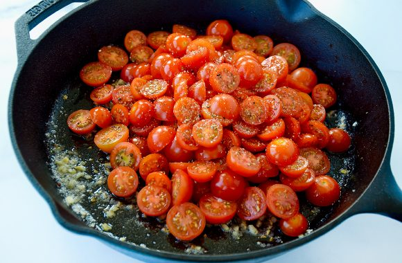 Sliced cherry tomatoes in large skillet with butter