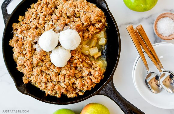 Homemade apple and pear crisp topped with ice cream next to plate with spoons
