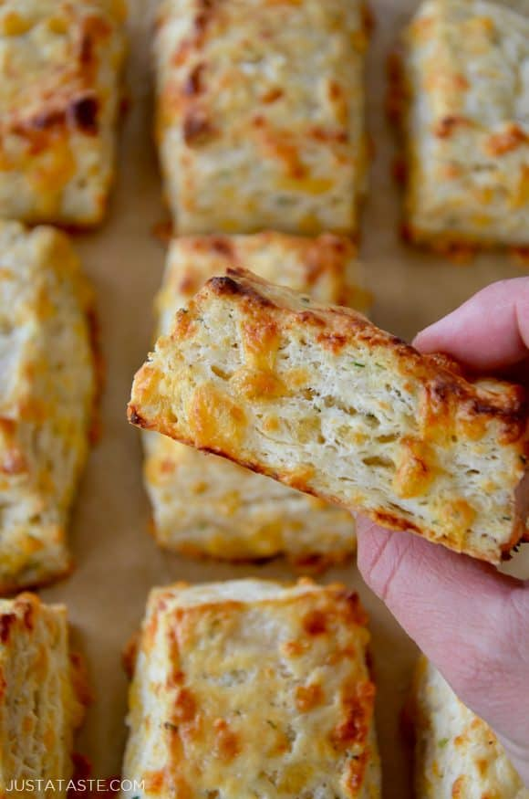 Hand holding easy cheddar biscuits with flaky layers