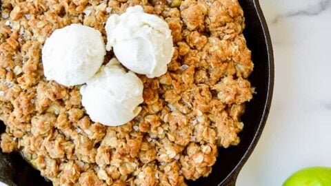 Homemade apple and pear crisp topped with vanilla ice cream next to green apples