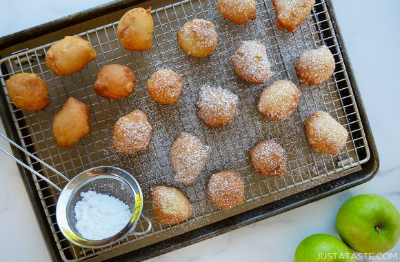 The best 30-minute apple fritters dusted with confectioners' sugar on top of baking sheet