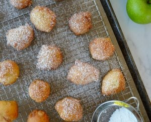 30-Minute Apple Fritters dusted with confectioners' sugar on baking sheet next to Granny smith apples