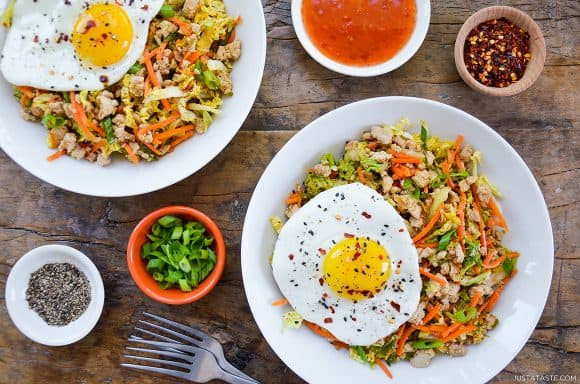 Easy healthy egg roll in a bowl topped with a fried egg next to dipping sauce and spices