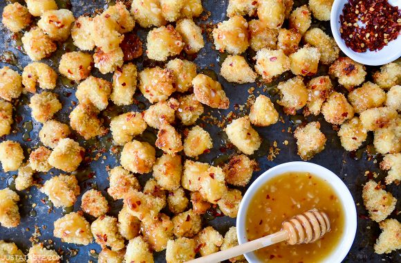 Easy baked popcorn chicken next to small ramekin with honey-garlic glaze