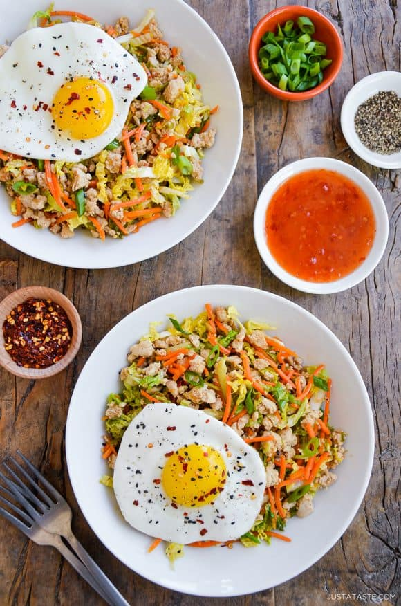Two servings of Healthy Egg Roll In a Bowl topped with a fried egg next to small ramekins with spices