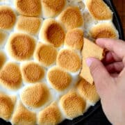 A hand dipping a graham cracker into a skillet containing Peanut Butter Cup S'mores Dip.