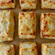 Rows of The Best Cheddar Biscuits on parchment paper-lined baking sheet