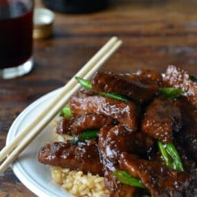 30-Minute Mongolian Beef over brown rice in white bowl with chopsticks