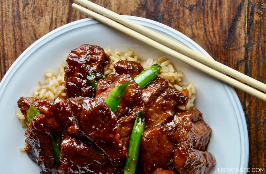 Top-down view of Mongolian beef garnished with slices of scallions over a bed of brown rice in a white serving bowl with chopsticks