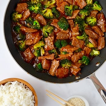 A skillet containing beef and broccoli with a bowl of white rice next to it