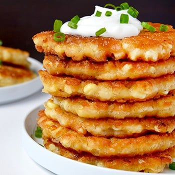 A stack of corn fritters topped with sour cream and chives