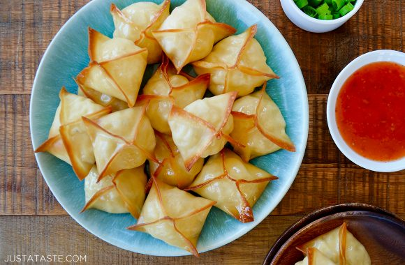 Easy baked crab rangoon on blue serving plate next to a small bowl with sweet and sour sauce
