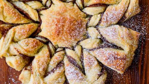 A top-down view of a puff pastry dessert dusted with confectioners' sugar