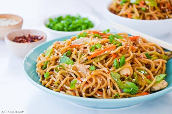 Easy Chicken Chow Mein topped with sesame seeds in blue bowl with chopsticks