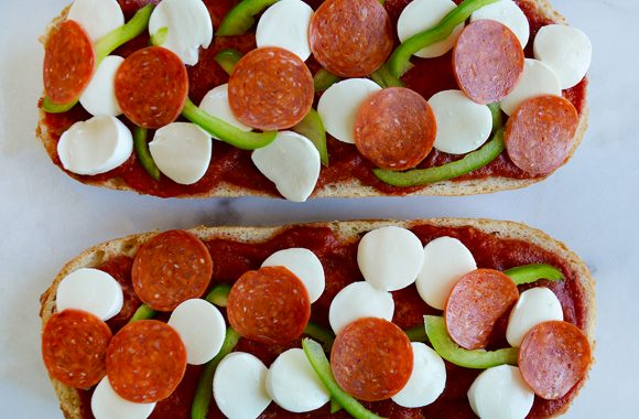Unbaked French bread pizza topped with green peppers, pepperoni and mozzarella