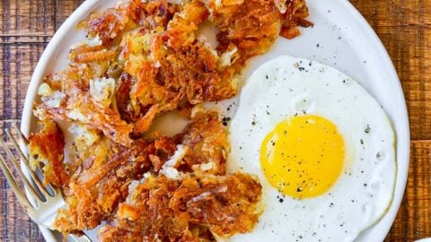 Top down view of a white plate containing the best crispy hash browns, a fork and a fried egg