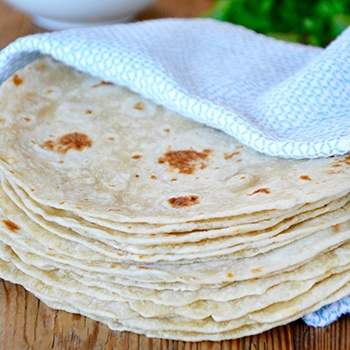 A stack of homemade flour tortillas wrapped in a blue towel