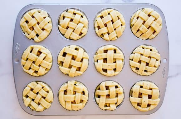 Muffin tin apple pies topped with weaved pie dough