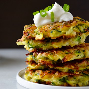 A stack of zucchini fritters topped with sour cream and scallions