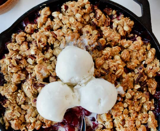 A cranberry crisp with ice cream on top and spoons sticking out