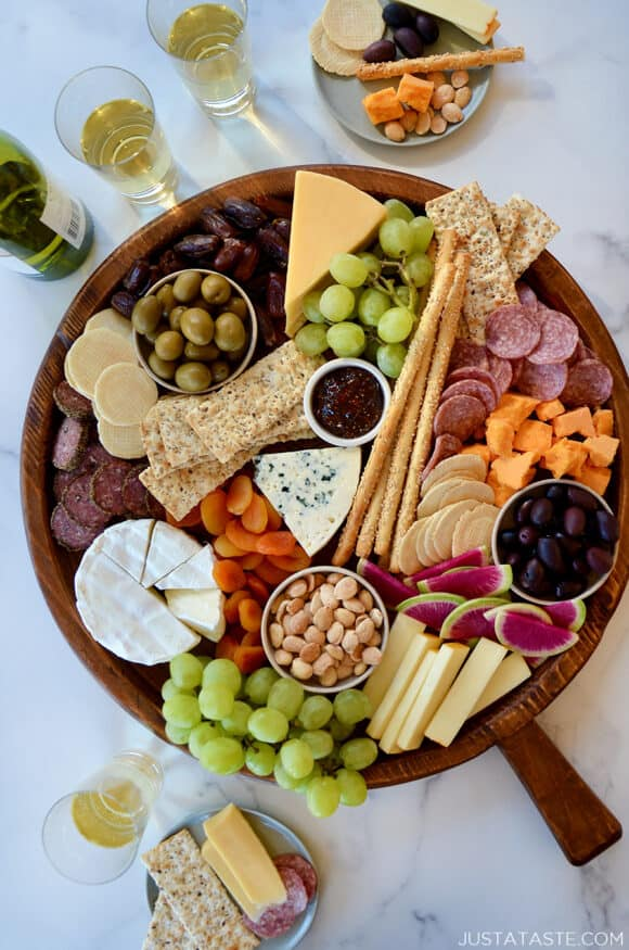 A top down view of a charcuterie board filled with meat, cheese, fruit and crackers