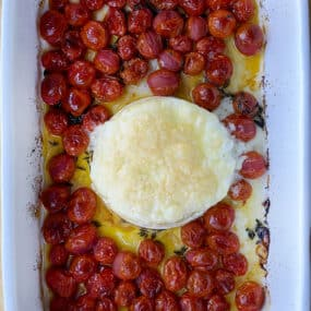 A top-down view of baked brie and roasted tomatoes in a baking dish