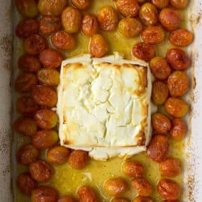 Baked feta in a baking dish with tomatoes
