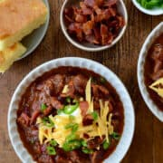 Chipotle Chili con Carne in large bowl topped with sour cream, cheddar cheese and sliced scallions