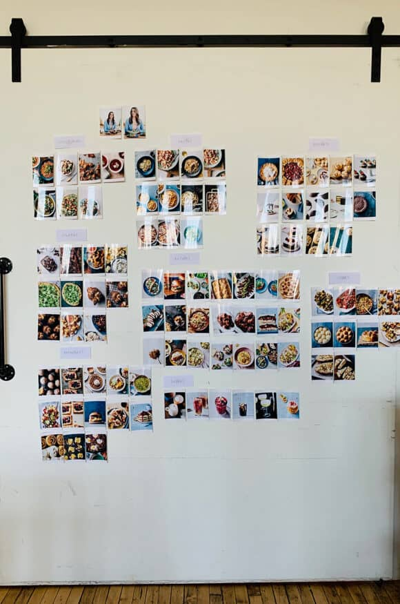 A white wall containing all of the photos from The Secret Ingredient Cookbook photo shoot