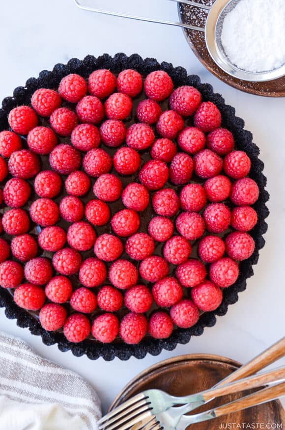 Top-down view of Easy No-Bake Chocolate Tart with Raspberries next to small plates with forks