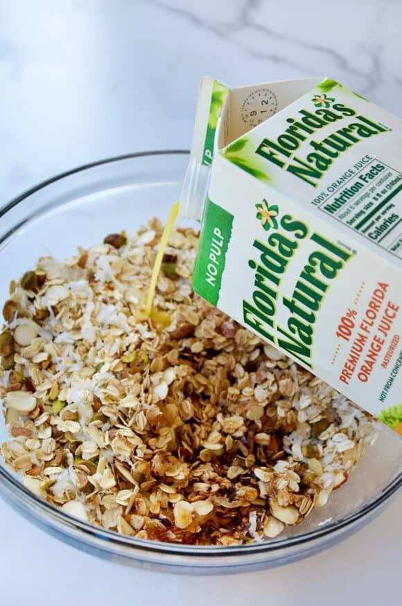 A carton of orange juice being poured into a bowl with granola ingredients